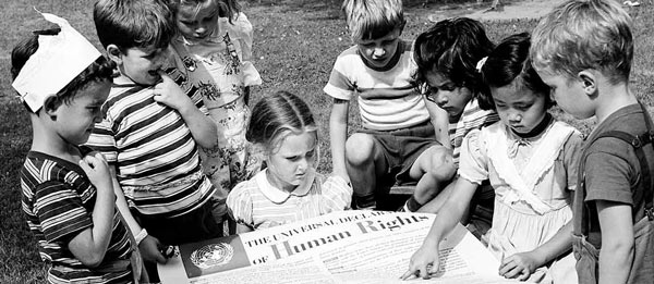 Children from the United Nations International Nursery School look at a poster of the Universal Declaration of Human Rights. (1950) UN Photo
